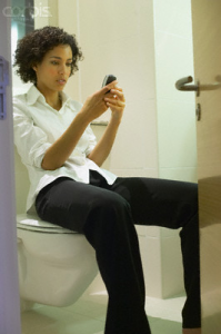 Woman using a mobile while on the loo