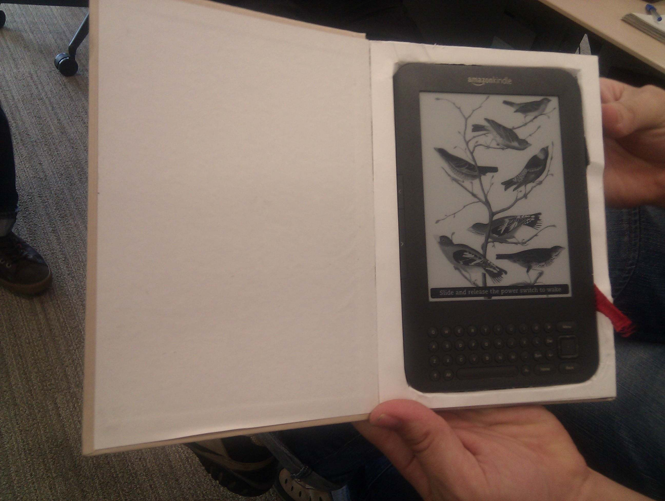 A Kindle nestled in a hollowed out paper book.