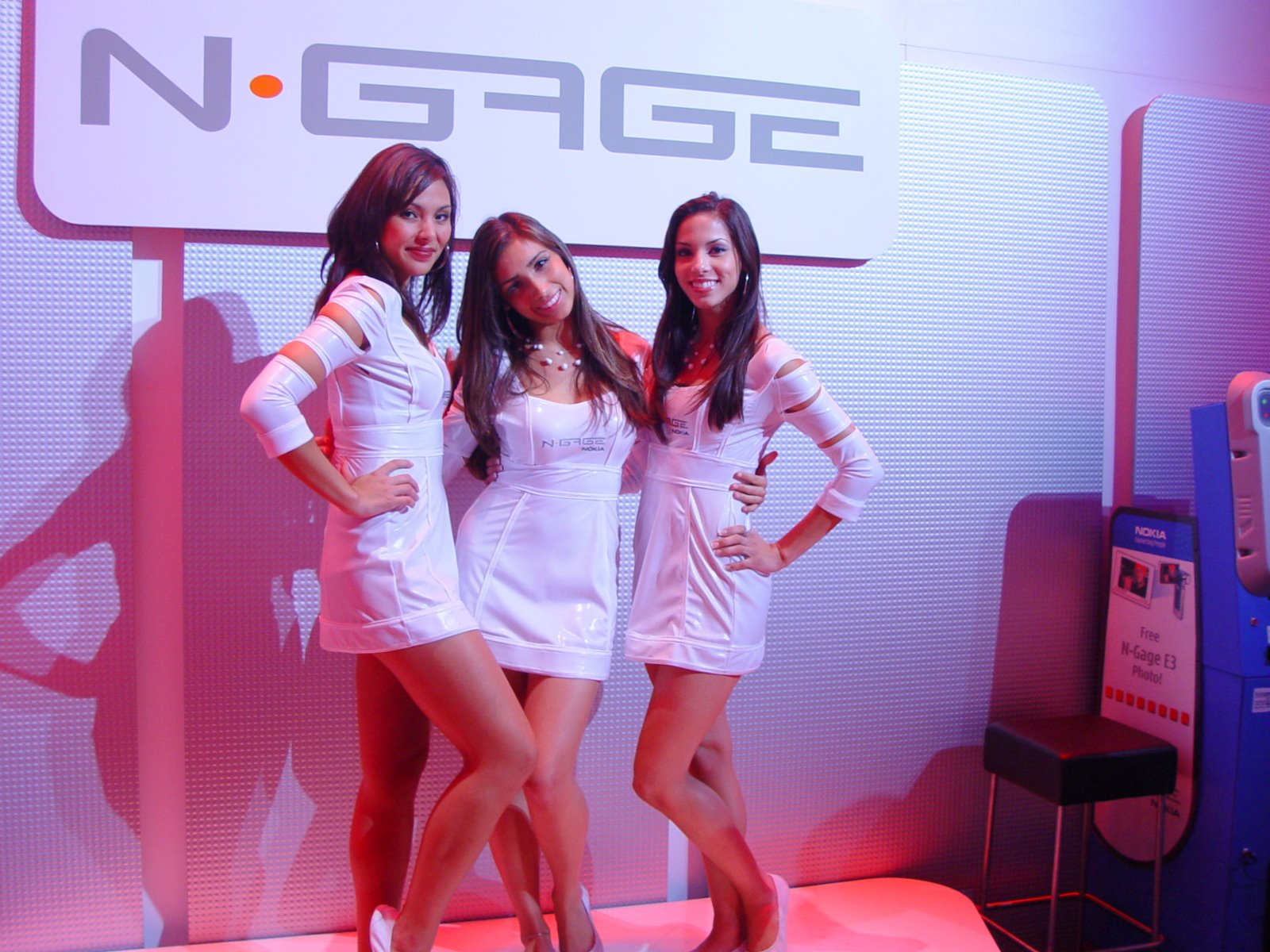 Three attractive women standing in front of a Nokia N-Gage sign