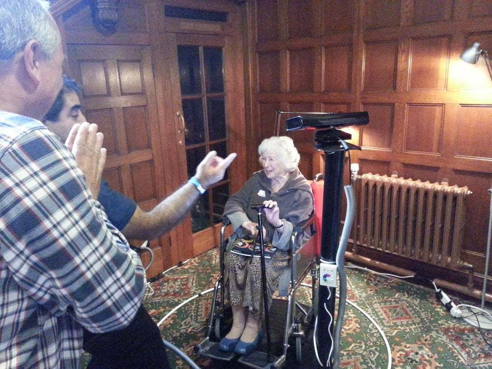 An old woman in a wheelchair smiles as she is 3D scanned.