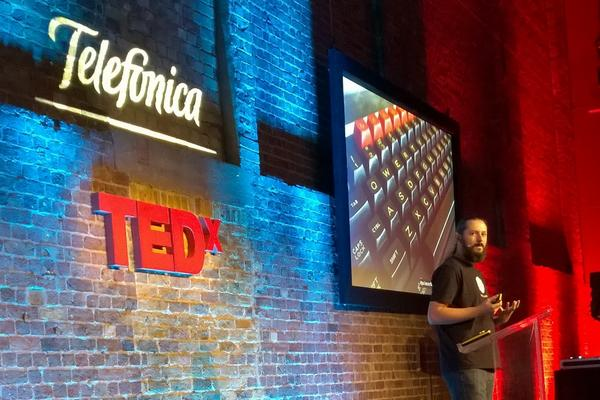 Terence Eden standing in front of the TEDx logo. A projection screen shows the keyboard of an old fashioned BBC Micro computer