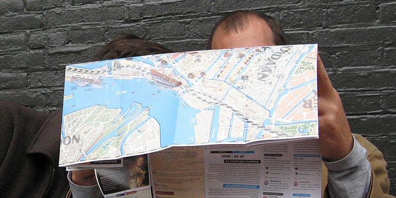 Two men are confused by a paper map