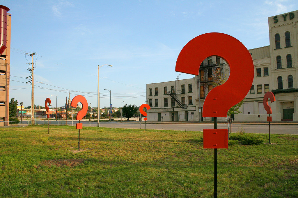 Some giant question marks standing in a field.