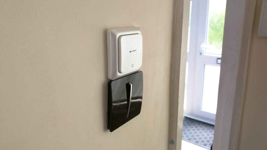 A regular light switch in the on position. Above it is the WisQo switch stuck to the wall.