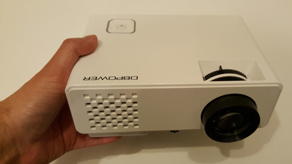 A small white projector held in the hand