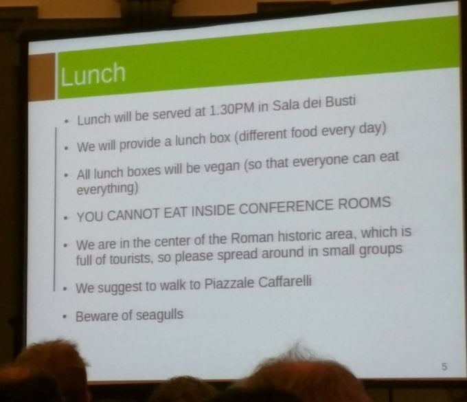 A projected screen at a conference, it says that all lunch boxes will be vegan.