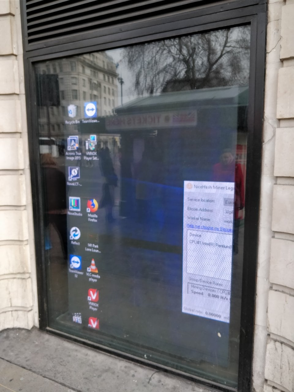 The display shows a windows desktop with a variety of icons. There is a window open