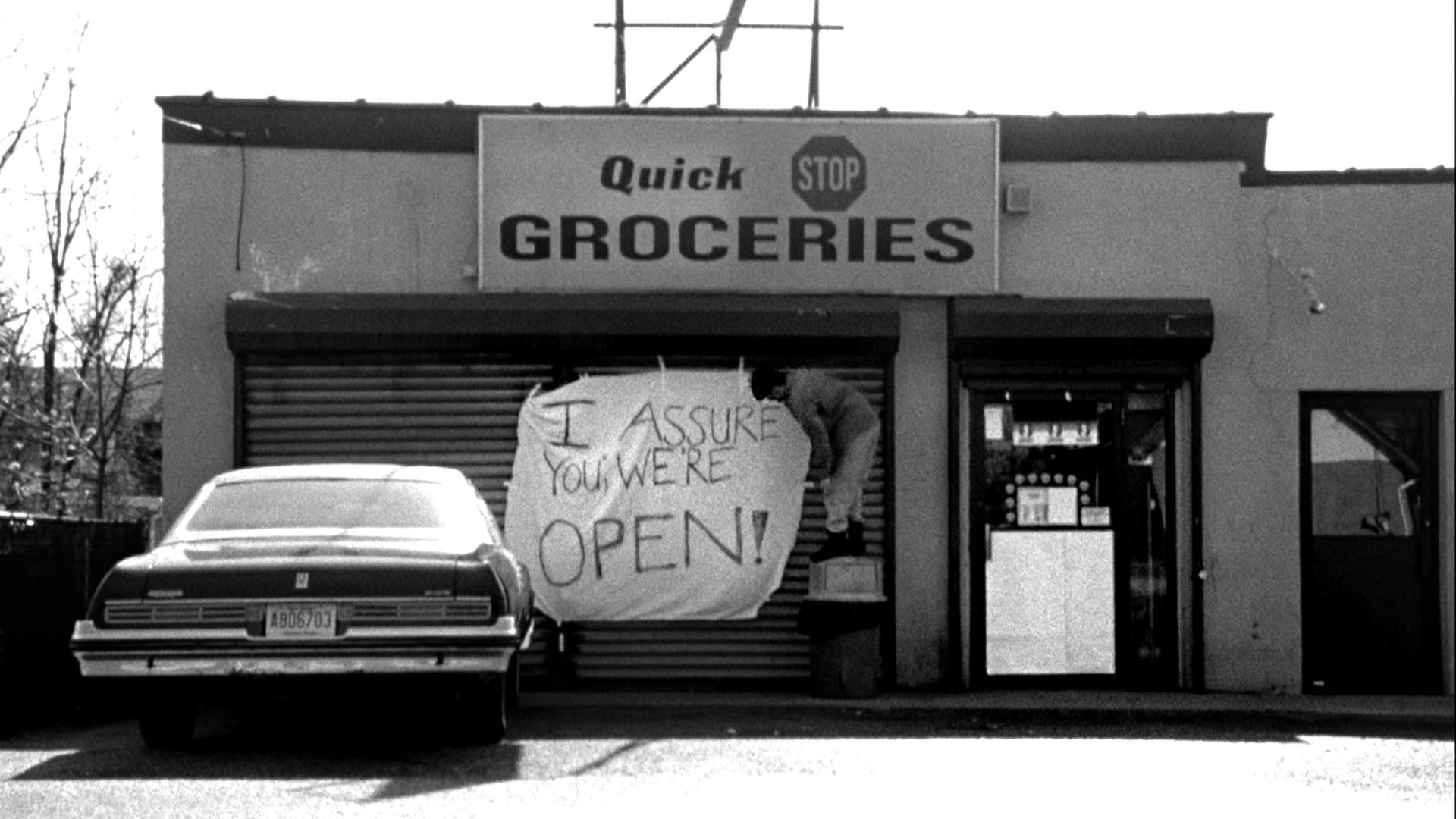 "Still from the movie ""Clerks"". A convenience store has the shutters closed. A handwritten sign says ""I assure you we're open!"""