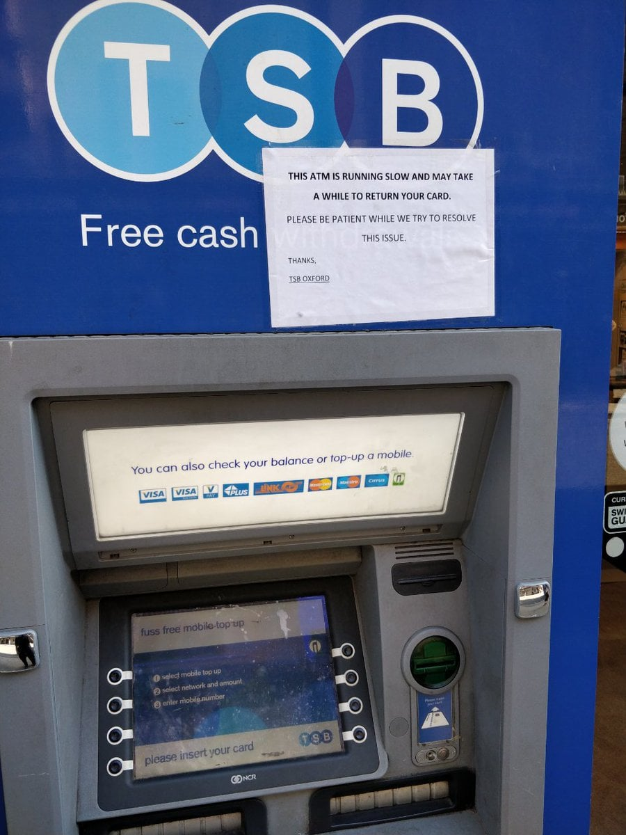 A sign is taped haphazardly to an ATM. It warns people that the ATM is slow and may take a while to return their card. There is no branding on the sign.