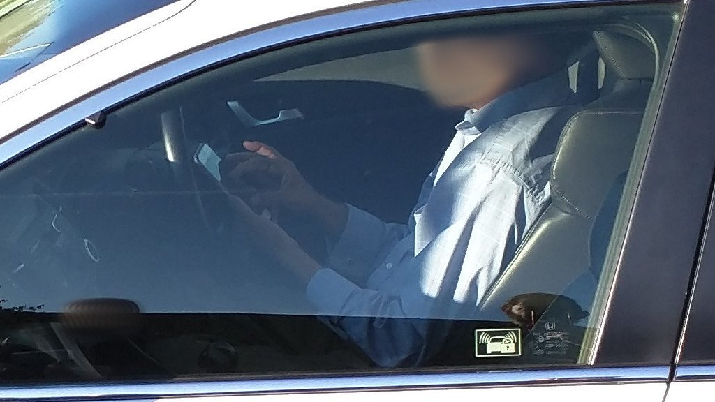 Detail of a Man playing with phone while driving.