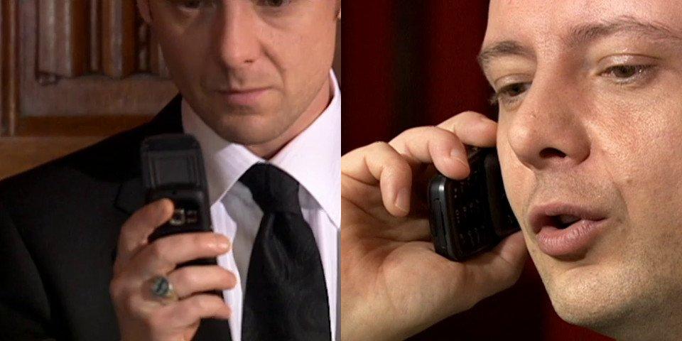 John Simm holding a black phone.
