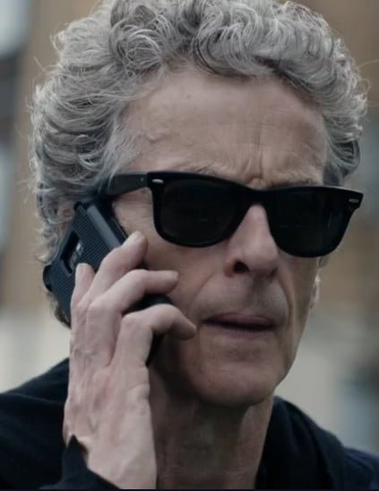 The doctor wearing sunglasses and holding a phone.