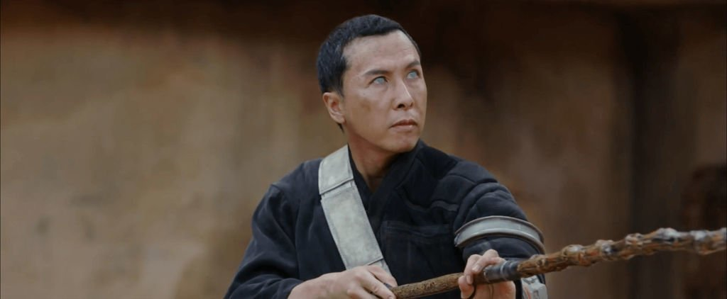Chirrut Îmwe, a blind monk, stands holding a wooden staff in a warrior's pose.