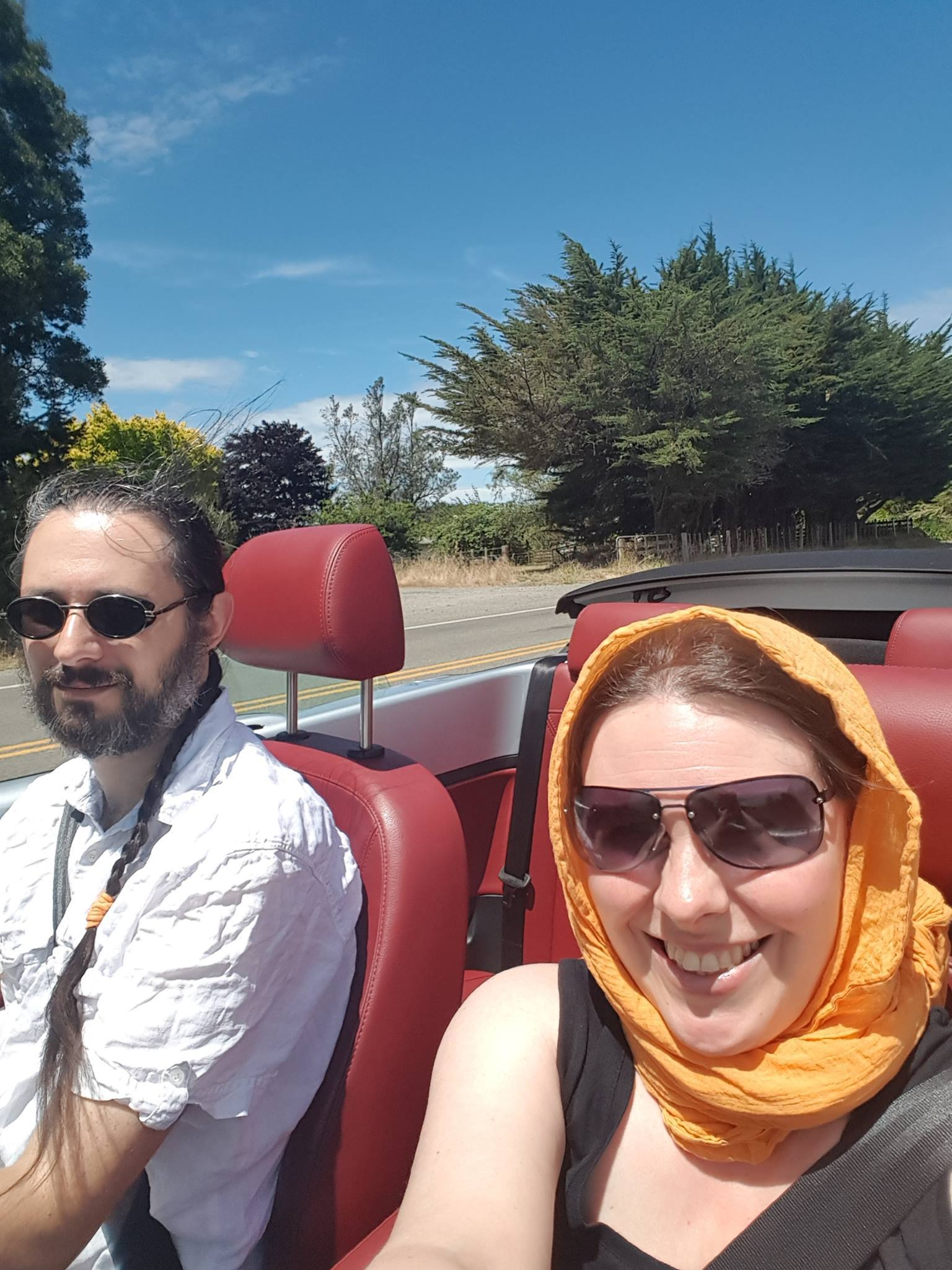 Terry and Liz in a convertable car, their hair flowing.