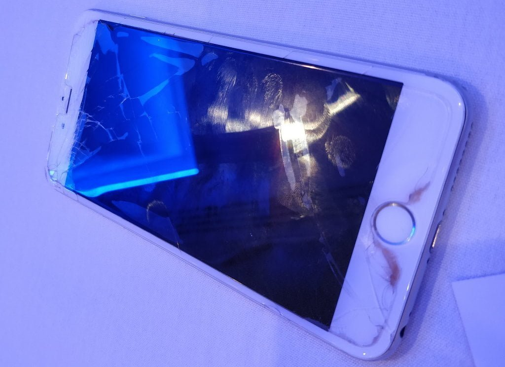 A modern iPhone. The screen is cracked, it is covered with a dirty screen protector covered in fingerprint smudges.