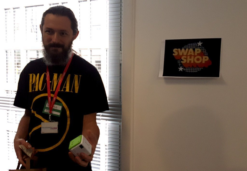"A bearded geek holding a mysterious cube. A sign in the background says ""Swap Shop""."