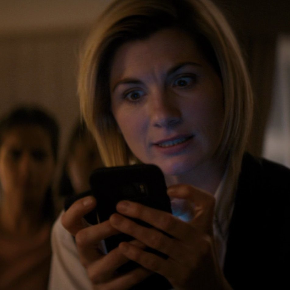 The Doctor holding Ryan's phone.