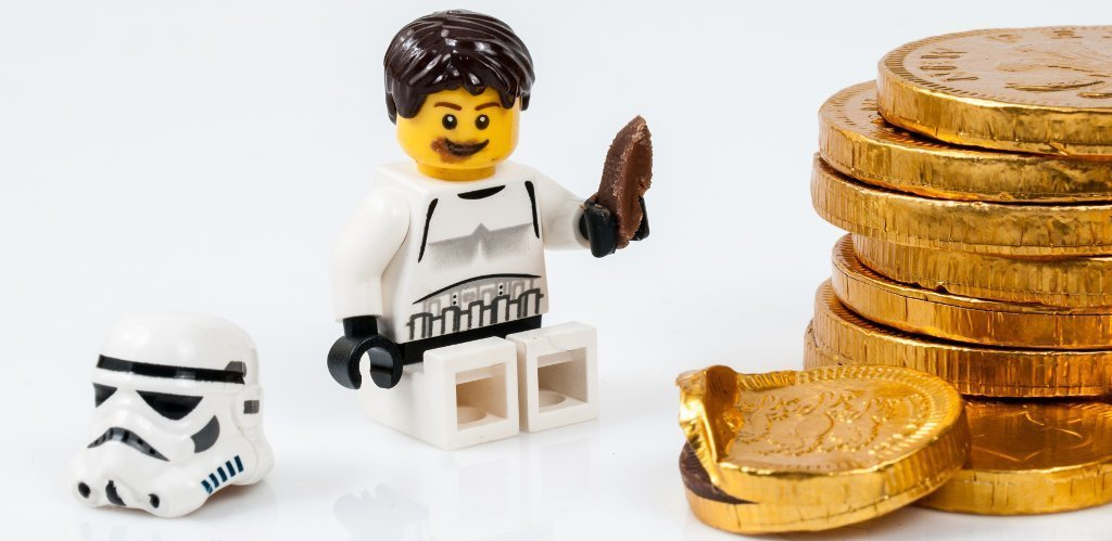 A tiny lego Storm Trooper eats a chocolate coin.