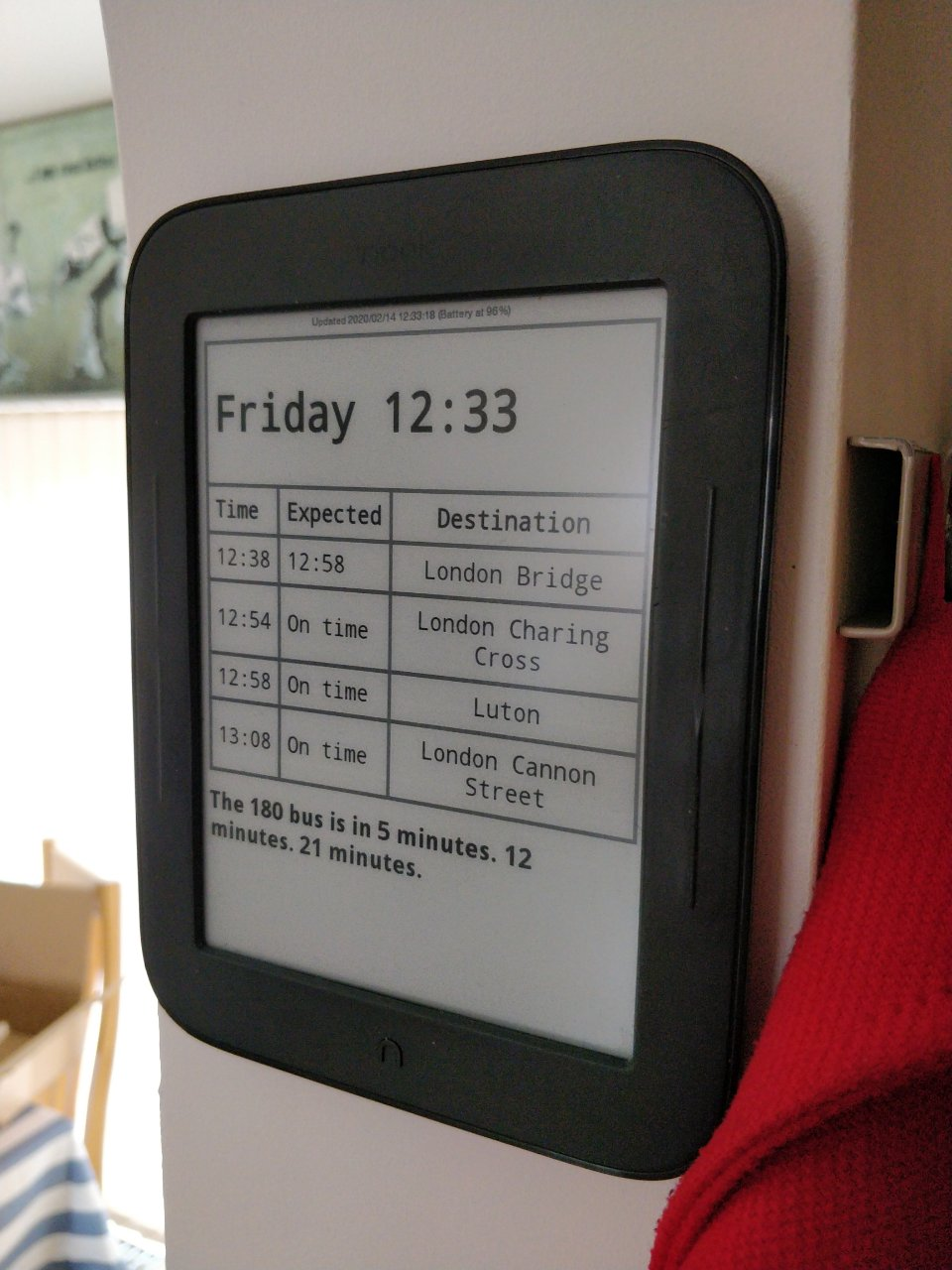 EInk screen showing bus and train times.