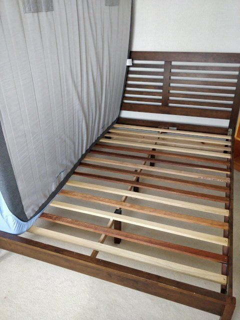 Mattress removed from bed exposing slats.