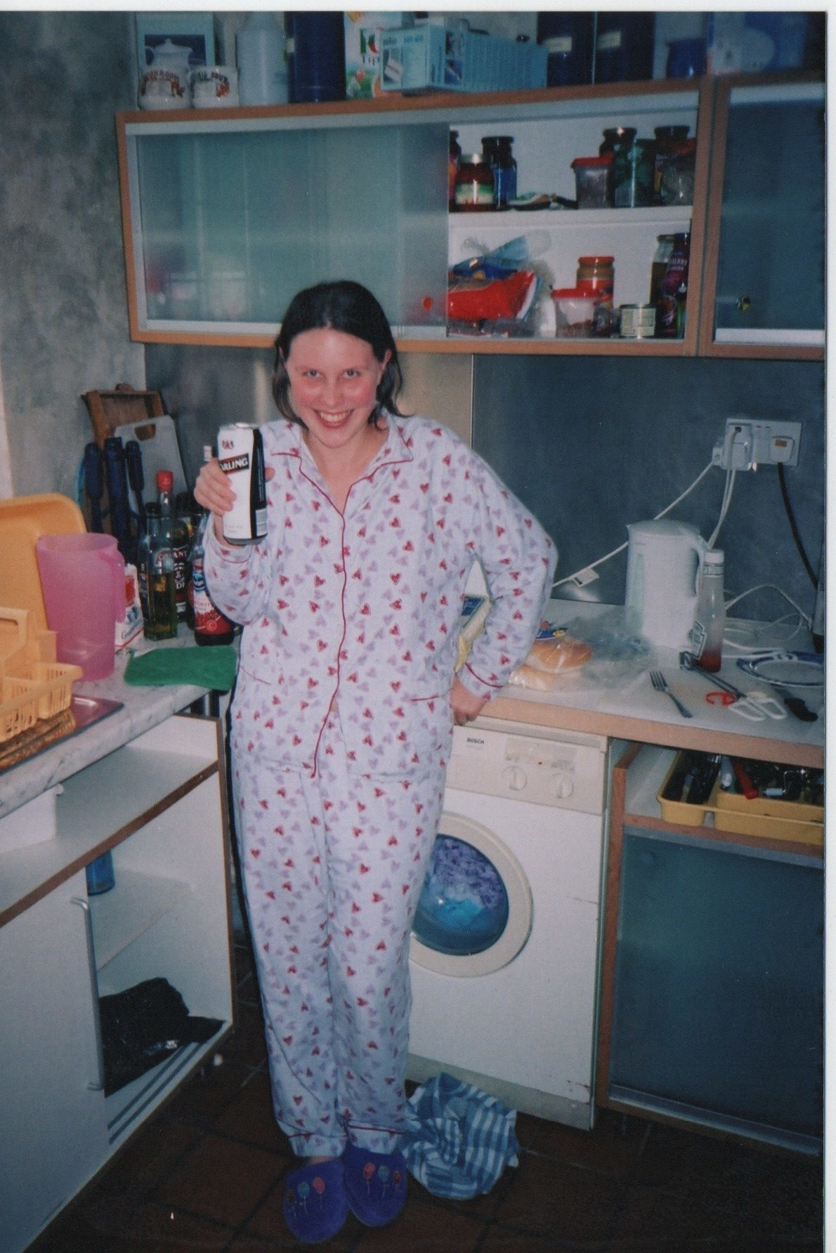 Liz drinking a can of Carling lager in the kitchen after finals.