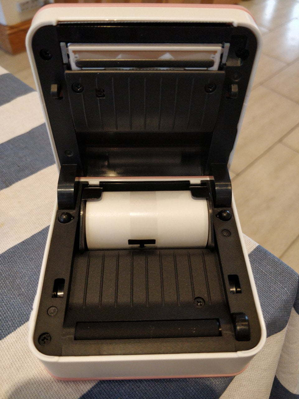 An open thermal printer with a small roll of paper.