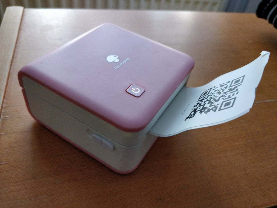 A hand-held pink cube with paper coming out of it.