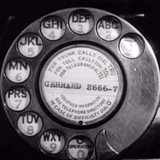 A black and white photo of an old rotary dial phone.