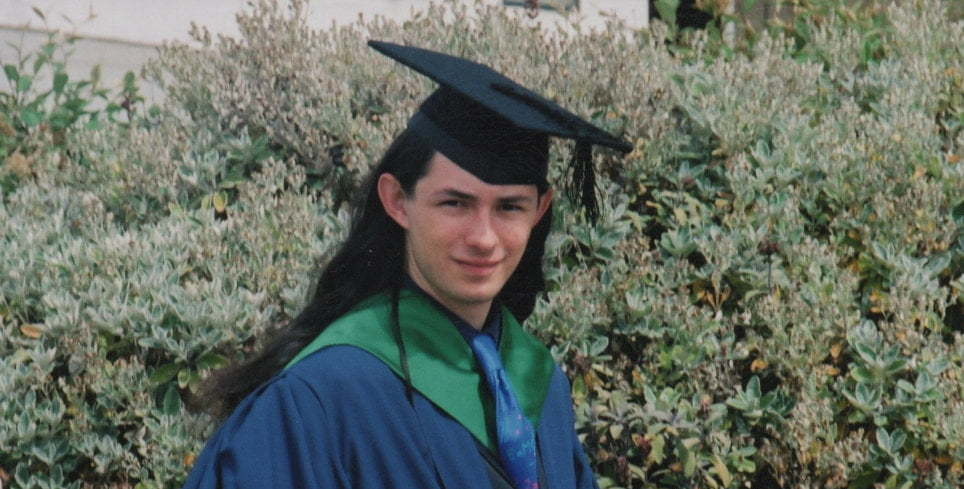 A young, beardless Terry - wearing graduation robes.