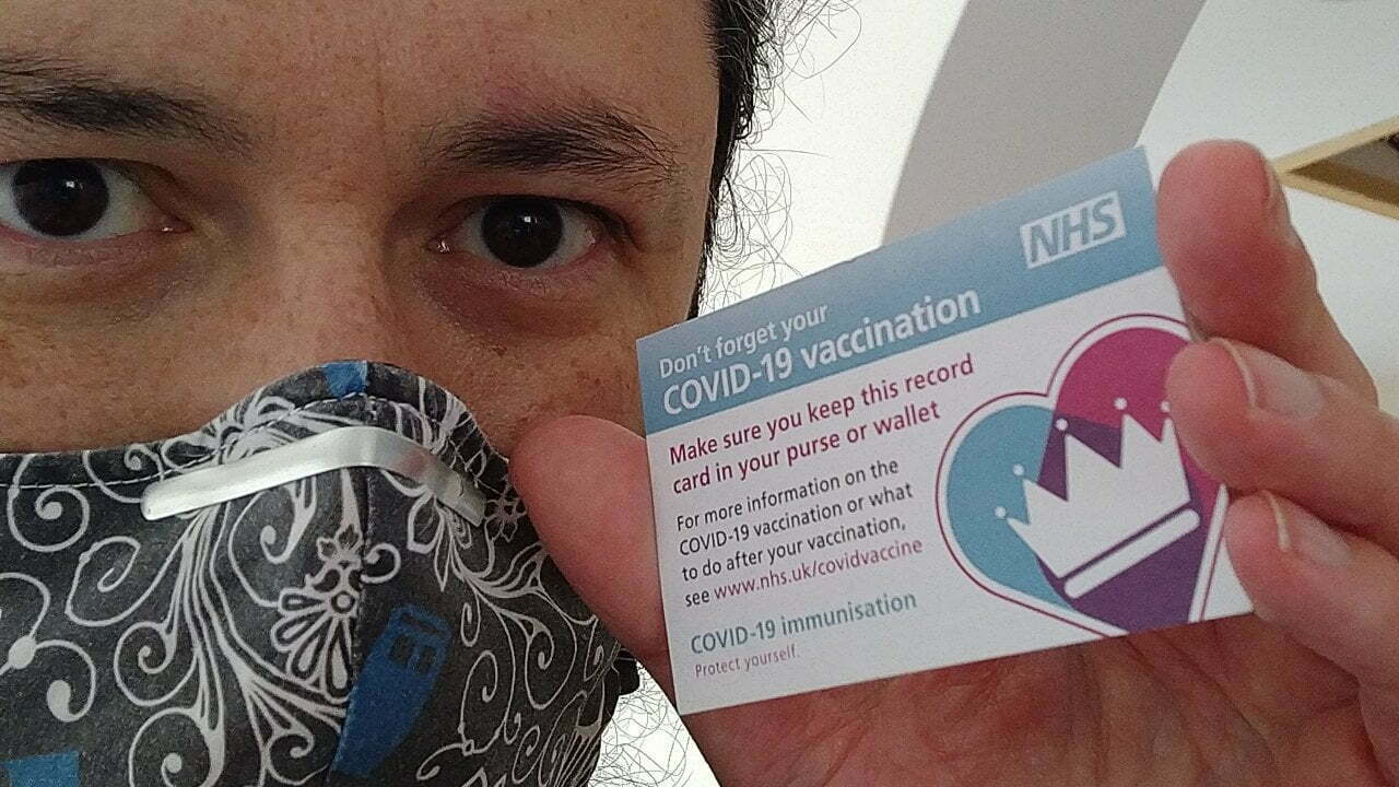 Me holding my NHS vaccination card.