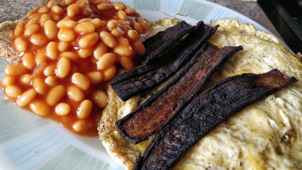 Cooked banana skins on an plate with eggs and beans.