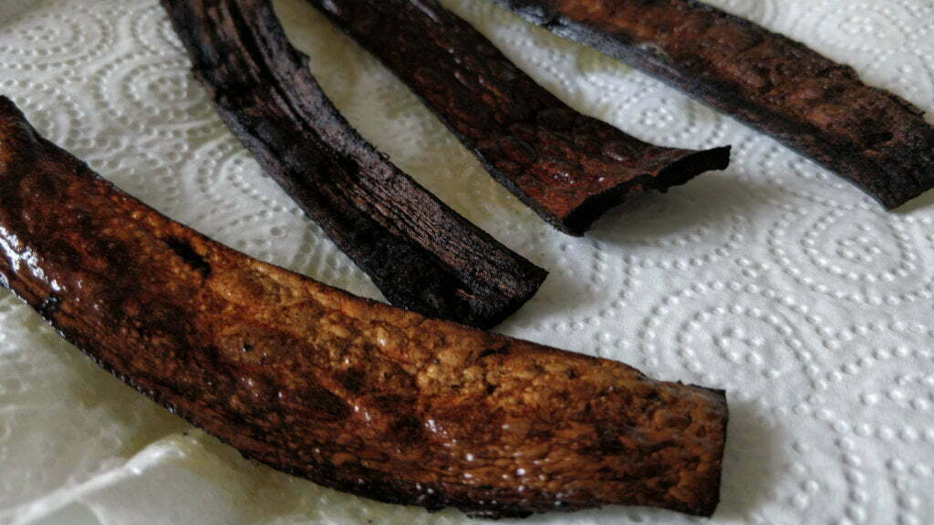 Cooked banana skins in a variety of dark shades, drying on a paper towel.