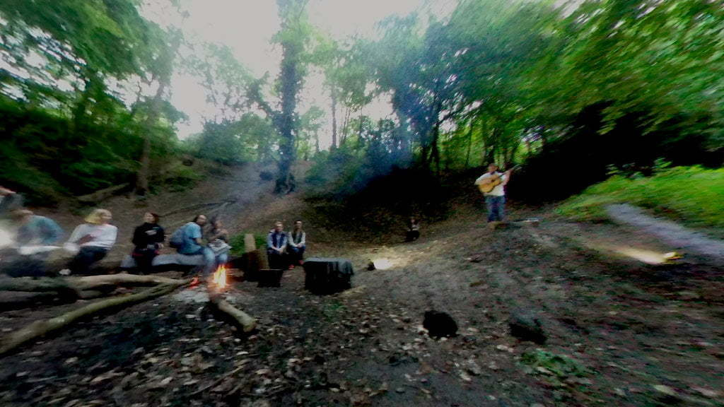 People sat around a fire in an abandoned chalk pit. A man stands and plays guitar.