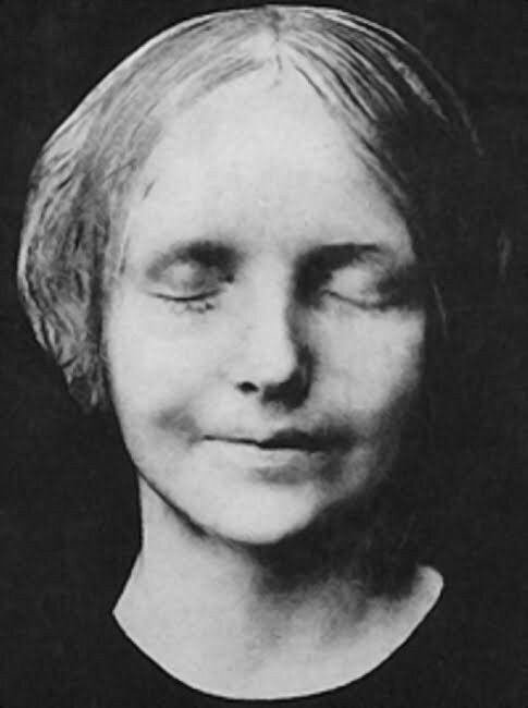 Black and white photo of the face of a young woman. Her eyes are closed and she is gently smiling.
